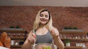 A mulher apta nova está preparando uma salada do vegetariano por vegetais verdes frescos usando o azeite após o exercício Bem-est video estoque