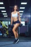 Mulher apta nova no short desportivo e em pesos guardando superiores ao estar no gym foto de stock