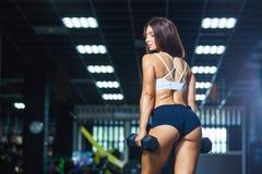 Mulher apta nova no short desportivo e em pesos guardando superiores ao estar na opinião traseira do gym foto de stock