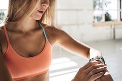 A mulher apta olha o relógio esperto e conta-o acima das calorias gastas após a formação no gym ensolarado Conceito saudável Fotos de Stock Royalty Free