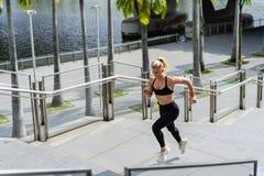 Mulher apta que corre acima as escadas na cidade fotografia de stock royalty free