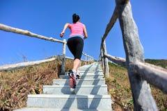 Mulher apta que corre acima em escadas da montanha foto de stock royalty free