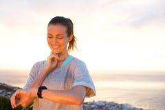 Mulher apta que cronometra sua frequência cardíaca com relógio Imagem de Stock