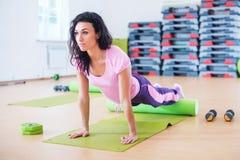 A mulher apta que estica no assoalho usando o rolo da espuma que faz o exercício da prancha, empurra levanta fotos de stock