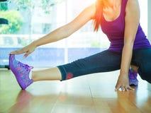 Mulher apta que estica seu pé para aquecer-se na sala do gym com equipamentos da aptidão no fundo fotos de stock royalty free