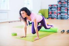 Mulher apta que exercita fazendo o exercício do núcleo no clube de aptidão fotografia de stock