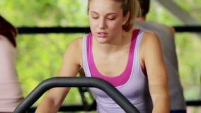 Mulher apta que faz a bicicleta de exercício video estoque