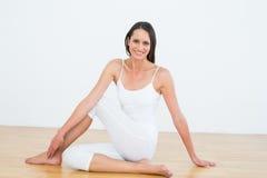 Mulher apta que faz a meia pose espinal da torção no estúdio da aptidão foto de stock