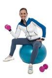 A mulher apta que faz o bíceps exercita com dumbbells cor-de-rosa fotografia de stock