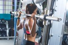 Mulher apta que faz o exercício da imprensa do ombro com uma máquina de Smith da barra do peso no gym foto de stock royalty free
