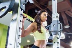Mulher apta que faz o exercício da imprensa do ombro com uma máquina de Smith da barra do peso no gym imagens de stock royalty free