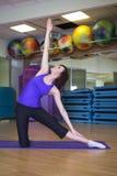 Mulher apta que faz o exercício da ioga em uma esteira em um Gym Fotografia de Stock Royalty Free
