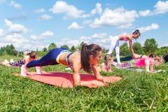 A mulher apta que faz o exercício da prancha, trabalhando na seção mestra abdominal muscles Exercício do núcleo da menina da apti foto de stock