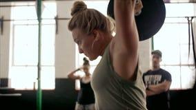 Mulher apta que faz o exercício do levantamento de peso no gym vídeos de arquivo