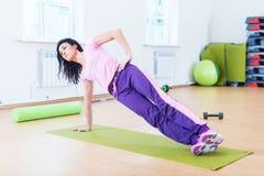 Mulher apta que faz o exercício do núcleo da prancha que treinam para trás e os músculos da imprensa fotos de stock