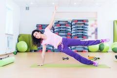 Mulher apta que faz o exercício do núcleo da prancha que treinam para trás e os músculos da imprensa imagens de stock royalty free
