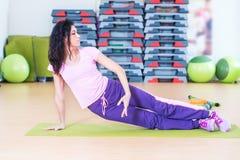 Mulher apta que faz o exercício do núcleo da prancha que treinam para trás e os músculos da imprensa fotografia de stock