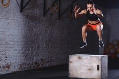Mulher apta que faz o exercício do salto da caixa A mulher muscular que faz a caixa salta no gym fotos de stock
