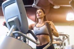 Mulher apta que faz o exercício em um instrutor elíptico Fotos de Stock