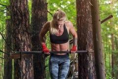 Mulher apta que faz o músculo acima na barra horizontal Imagem de Stock