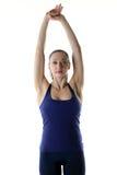 Mulher apta que guarda ambos sua mão acima no ar para esticar Fotos de Stock Royalty Free