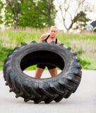 Mulher apta que lança o pneu fora Fotos de Stock Royalty Free