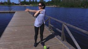 A mulher aquece-se antes do exercício no parque perto do lago vídeos de arquivo