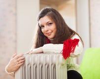 A mulher aquece-se perto do calefator morno imagem de stock