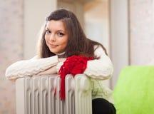A mulher aquece-se perto do calefator morno imagens de stock royalty free
