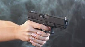 A mulher armada dispara com arma em um alvo, movimento lento filme