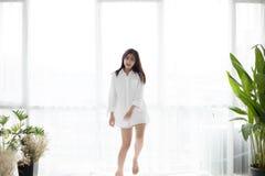 A mulher asiática acorda em sua cama descansada inteiramente e abre a cortina fotos de stock royalty free