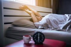 A mulher asiática acorda o estiramento oneself e boceja em seu quarto com o despertador do preto do borrão fotos de stock