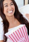 Mulher asiática alegre que come o milho de PNF fotografia de stock