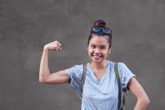Mulher asiática alegre que sorri ao dobrar seu bíceps fora foto de stock royalty free