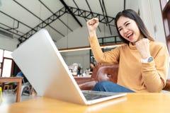 Mulher asiática atrativa nova que olha o laptop que sente alegre feliz ou excitado no projeto pelo sucesso das mãos do gesto ou fotografia de stock royalty free