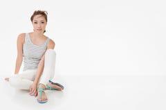 A mulher asiática atrativa senta-se na terra imagem de stock