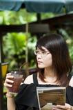 A mulher asiática bonita aprecia o chá gelado. Fotos de Stock