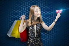 Mulher asiática bonita com os sacos de compras que mostram seu cartão de crédito fotos de stock royalty free