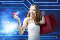 Mulher asiática bonita com os sacos de compras que mostram seu cartão de crédito imagem de stock