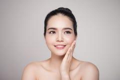 Mulher asiática bonita de sorriso feliz que toca em sua cara foto de stock royalty free