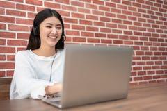 A mulher asiática bonita de sorriso na camisa branca está trabalhando no lapto foto de stock royalty free