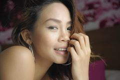 A mulher asiática bonita e doce nova com brincos e compõe o sorriso feliz e alegre olhando a câmera imagem de stock