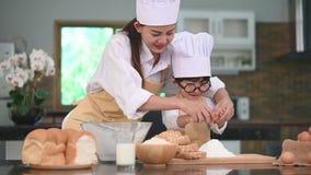 A mulher asiática bonita e o rapaz pequeno bonito com monóculos preparam-se ao cozimento na cozinha em casa junto Estilos de vida video estoque