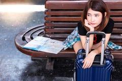 A mulher asiática bonita está esperando algum táxi ou ônibus para pegará-la imagens de stock
