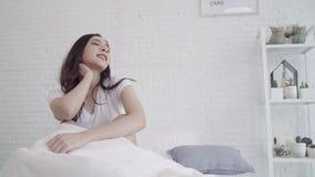 A mulher asiática bonita feliz acorda, sorrindo e esticando seus braços em sua cama no quarto vídeos de arquivo
