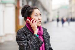 Mulher asiática bonita feliz que chama pelo telefone no stree da mola Fotos de Stock