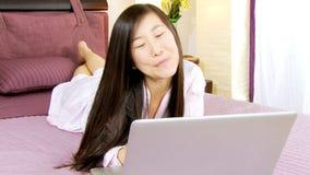 Mulher asiática bonita na cama com portátil filme