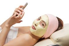 Mulher asiática bonita na máscara facial, mulher que usa o app no telefone esperto móvel Fotos de Stock Royalty Free