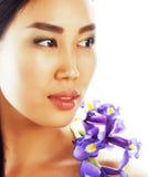 A mulher asiática bonita nova com fim da orquídea da flor isolou acima o sp Imagem de Stock