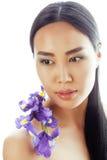 A mulher asiática bonita nova com fim da orquídea da flor isolou acima termas Imagem de Stock Royalty Free